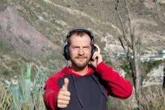Ein bärtiger Mann hört Musik auf Kopfhörern, in der Natur Es gibt Berge hinter es Er zeigt sich seinen Daumen lizenzfreies stockfoto