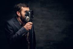 Ein bärtiger Mann kleidete in einer Klage hält Videokamera der Weinlese 8mm an Lizenzfreie Stockfotos