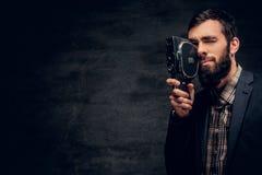 Ein bärtiger Mann kleidete in einer Klage hält Videokamera der Weinlese 8mm an Stockfoto