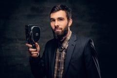 Ein bärtiger Mann kleidete in einer Klage hält Videokamera der Weinlese 8mm an Lizenzfreies Stockbild