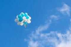 Ein Bündel blaue und weiße Ballone im Himmel Stockbilder