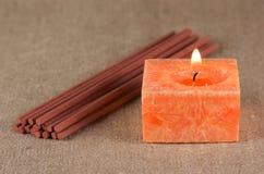 Ein Bündel der Duftsteuerknüppel und der Kerze Stockfotografie