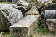 Ein Bündel des alten Steins blockiert das Lügen auf dem Gras Stockfotografie