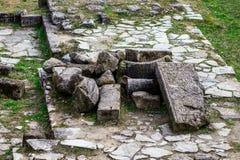 Ein Bündel des alten Steins blockiert das Lügen auf dem Gras Stockfoto