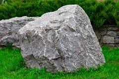 Ein Bündel des alten Steins blockiert das Lügen auf dem Gras Lizenzfreie Stockfotos