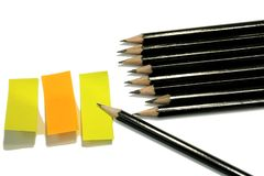 Ein Bündel des Skizzierens von Bleistiften und von drei klebrigen Anmerkungen in Gelbem und in Orange stockfoto