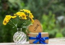 Ein Bündel gelbe Blumen, Geschenk und hölzernes Herz Romantisches Konzept Lizenzfreie Stockfotos