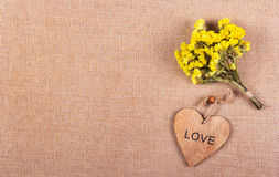 Ein Bündel gelbe Blumen und ein hölzernes Herz auf einem natürlichen Leinenhintergrund Romantisches Konzept Stockfotos