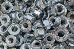 Ein Bündel glänzende neue Metallsechskantmuttern, die chaotisch liegen Stockbild