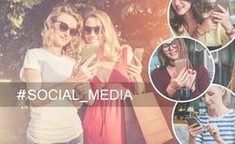 Ein Bündel Leute, habend Gespräche Stand mit zwei jungen Frauen draußen und Gebrauch Smartphone Mädchen mit Smartphones Stockfotografie
