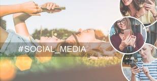 Ein Bündel Leute, habend Gespräche Zwei junge Frauen liegen auf dem Rasen, hören Musik und benutzen einen Smartphone Stockfoto