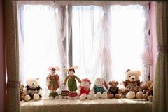 Ein Bündel Puppen im Fenster Lizenzfreie Stockfotos