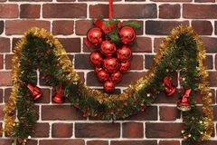 Ein Bündel rote Bälle und eine Girlande mit Weihnachtsglocken auf einer Backsteinmauer Stockbilder