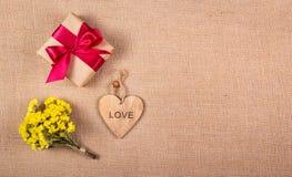 Ein Bündel Sommergelb blüht, eine Geschenkbox und ein hölzernes Herz Romantisches Konzept Hintergründe und Beschaffenheiten Stockfotografie