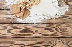 Ein Bündel Weizen und Mohnblume und Mehl goss aus Glas und Scheiben brot auf alten hölzernen Planken heraus lizenzfreie stockfotos