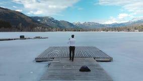 Ein Büroarbeiter auf einem hölzernen Dock auf einem ursprünglichen Eis umfasste Seewürfe weg von seiner Jacke und Bindung und Spr stock video