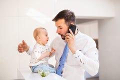 Ein Baby, das seine Väter macht, binden schmutziges beim Essen lizenzfreies stockbild