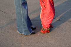Ein Baby draußen mit einer Mutter (geerntete Beine) Stockfotografie