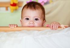 Ein Baby in einem Feldbett, das Peekaboo spielt und die Feldbettschienen saugt Stockfotografie