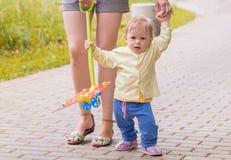 Ein Baby geht mit Mutter Stockfotos