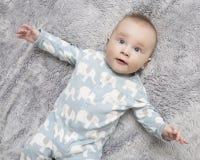 Ein Baby ist auf der grauen weichen Decke lizenzfreie stockbilder