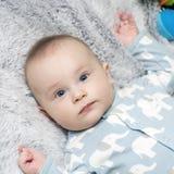 Ein Baby ist auf der grauen weichen Decke stockbilder