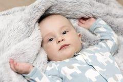 Ein Baby ist auf der grauen weichen Decke stockfotografie