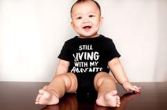 Ein Baby trägt ein Hemd mit einer Mitteilung, sagend, das er noch mit meinen Eltern lebt Stockfotos