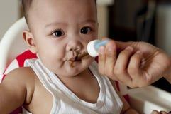 Ein Baby trinkt seine Vitamine unter Verwendung eines Tropfenzählers stockfotografie