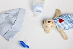 Ein Babyhut, Spielwaren, Friedensstifter auf einem weißen Hintergrund stockfotos
