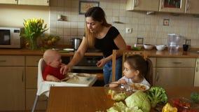 Ein Babysitter in der Küche - zwei Kinder mit dem Mittagessen einziehend und Abendessen vorbereitend Agentur, die Hauptpersonal m stock video