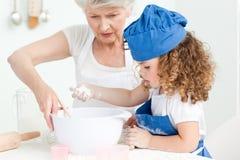 Ein Backen des kleinen Mädchens mit ihrer Großmutter Lizenzfreies Stockfoto