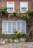 Ein Backsteinhaus mit Rosen auf der Eingangsterrasse, gesehen in Rye, Kent, Großbritannien Stockbild