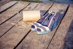 Ein Ball des Garns um Frauensandalen, Schuhe draußen Lizenzfreie Stockbilder
