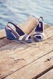 Ein Ball des Garns um Frauensandalen, Schuhe draußen Stockfotografie