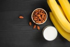 Ein banch von Bananen mit Mandeln und Milch auf hölzernem Hintergrund lizenzfreies stockfoto