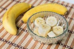Ein banch von Bananen und von geschnittenen Banane in einem Topf über einem hölzernen Hintergrund Lizenzfreie Stockfotos