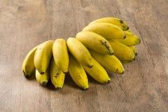 Ein banch von Bananen und von geschnittenen Banane in einem Topf über einer Tabelle Stockfotografie