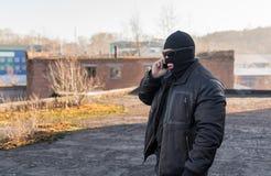 Ein Bandit in einer schwarzen Lederjacke und in einer Maske sprechend am Telefon auf der Straße nahe einem verlassenen Gebäude lizenzfreies stockfoto
