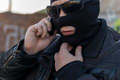 Ein Bandit in einer schwarzen Lederjacke und in einer Maske sprechend am Telefon auf der Straße nahe einem verlassenen Gebäude stockbilder