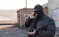 Ein Bandit in einer schwarzen Lederjacke und in einer Maske sprechend am Telefon auf der Straße nahe einem verlassenen Gebäude lizenzfreie stockbilder