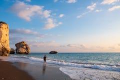 Ein barfüßigjunge spielt am Strand againt den PETRA-tou Romiou-Geburtsortrock der Aphrodite, der im Nachmittagslicht, herein geba lizenzfreie stockfotografie