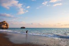 Ein barfüßigjunge spielt am Strand am der PETRA-tou Romiou-Geburtsortrock Aphrodite, in Paphos, Zypern stockbild