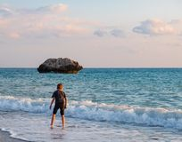 Ein barfüßigjunge spielt am Strand am der PETRA-tou Romiou-Geburtsortrock Aphrodite, in Paphos, Zypern lizenzfreie stockfotos