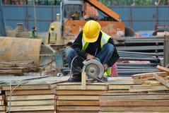 Ein Bauarbeiter, der die tragbare Allzweckrohrschneidermaschine verwendet Lizenzfreie Stockbilder
