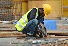 Ein Bauarbeiter, der die tragbare Allzweckrohrschneidermaschine verwendet Lizenzfreies Stockbild