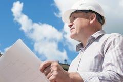 Ein Bauarbeitermann im weißen Sturzhelm, der Pläne auf einem Hintergrund mit blauem Himmel hält Lizenzfreie Stockfotografie