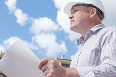 Ein Bauarbeitermann im weißen Sturzhelm, der Pläne auf einem Hintergrund mit blauem Himmel hält Stockfotografie