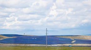 Ein Bauernhof von Batterien von Solarkraftwerken auf einem Feld unter einem Himmel voll von Wolken ?kostrom Alternative Energie lizenzfreie stockfotos