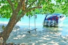 Ein Baum und ein Schwingen rope auf dem Strand und dem Schnellboot lizenzfreies stockbild